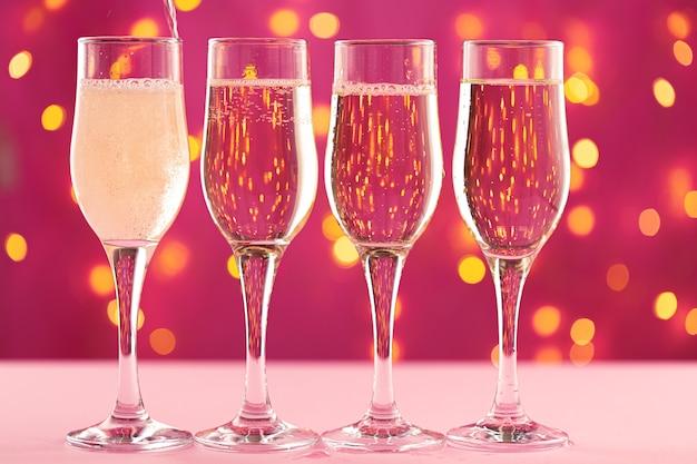 Quatre verres de champagne contre rose avec des lumières de guirlande floues