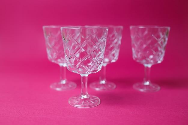 Quatre verres à vin sur fond rose avec espace de copie.