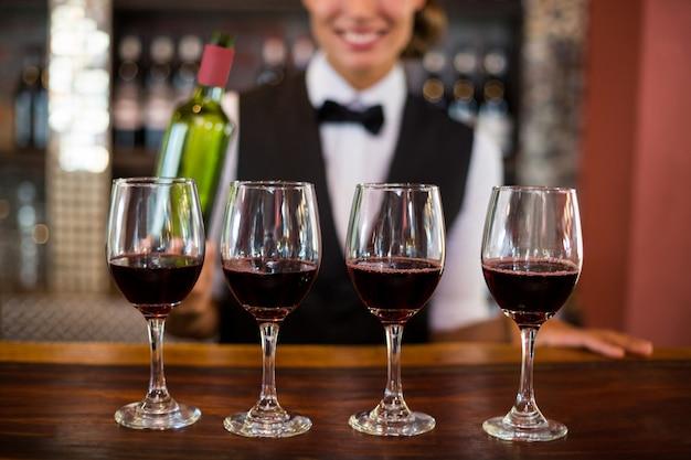 Quatre verres de vin rouge prêts à servir sur le comptoir du bar