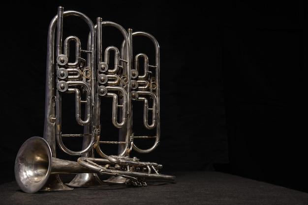 Quatre vieux instruments à vent en laiton se tiennent sur une table sur un fond noir