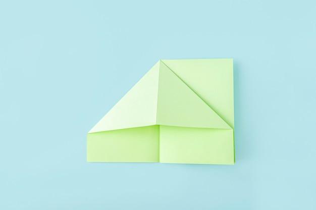 Quatrième étape de la fabrication d'un papillon en papier origami avec du papier vert, des ciseaux sur fond bleu
