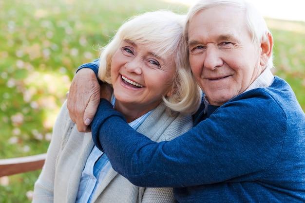 Que l'amour dure pour toujours. heureux couple de personnes âgées se liant les uns aux autres et souriant tout en étant assis sur le banc du parc ensemble