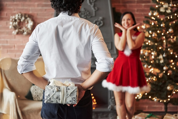 Ce que ça peut être. l'homme se tient et détient la boîte-cadeau derrière. une femme en robe rouge va maintenant recevoir un cadeau de noël de son petit ami
