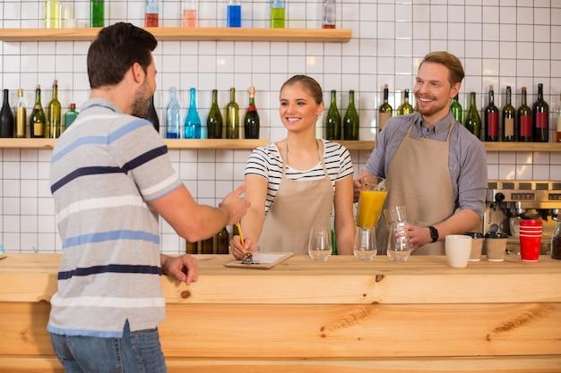 Que désirez-vous. positif ravi jeune femme souriante et regardant son client tout en prenant une commande de lui