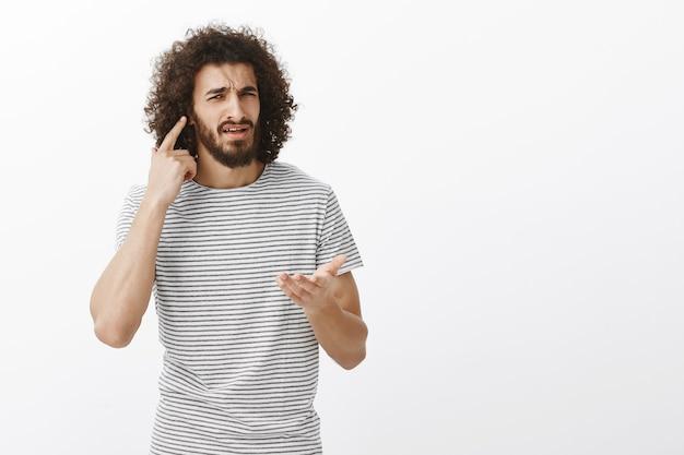 Ce que je ne peux pas vous entendre, que voulez-vous. portrait de confus gêné beau mec oriental avec coiffure afro, dirigeant à l'oreille et pointant avec palm