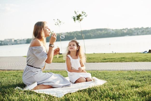 Que le lancement des bulles est arrivé. photo de jeune mère et sa fille s'amusant sur l'herbe verte avec lac en arrière-plan.