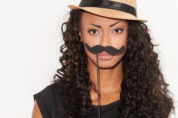 Que pensez-vous de ma moustache ? portrait d'une jeune femme africaine espiègle au chapeau funky tenant une fausse moustache sur son visage et regardant la caméra en se tenant debout sur fond blanc