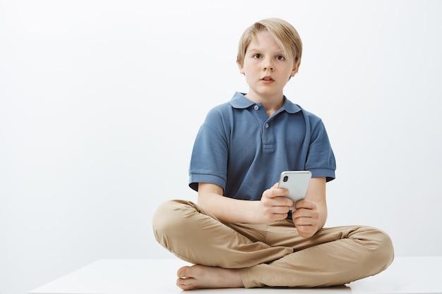 Que voulez-vous dire pas de bonbons. portrait de garçon mignon curieux interrogé avec des cheveux blonds assis sur le sol avec les pieds croisés, tenant le smartphone et regardant de côté confus