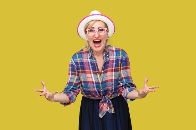 Que voulez-vous de moi? portrait d'une femme mature élégante et moderne en colère dans un style décontracté avec chapeau et lunettes debout, regardant la caméra et demandant. tourné en studio intérieur isolé sur fond jaune