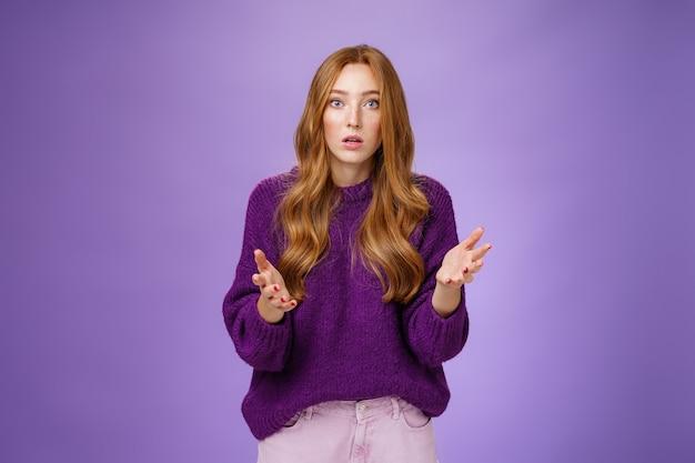 Quel mal, je m'inquiétais. portrait d'une jeune femme rousse nerveuse et empathique se sentant anxieuse levant les mains interrogées et regardant la caméra se demandait exprimer sa préoccupation pour un ami sur un mur violet.