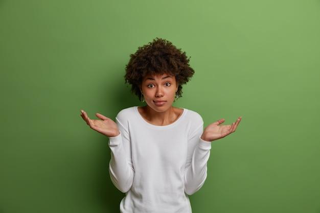 Quelle façon de choisir je me demande? une femme douteuse hésitante exprime l'incertitude, hausse les épaules, entend une question ridicule, se sent confuse, porte un pull blanc décontracté, isolé sur un mur vert