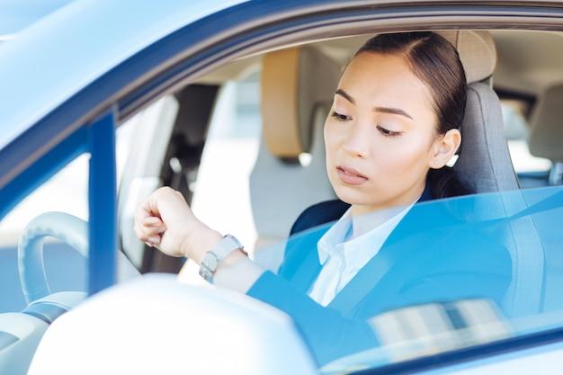 Quelle heure est-il. femme d'affaires prospère sérieuse en regardant sa montre tout en allant à une réunion