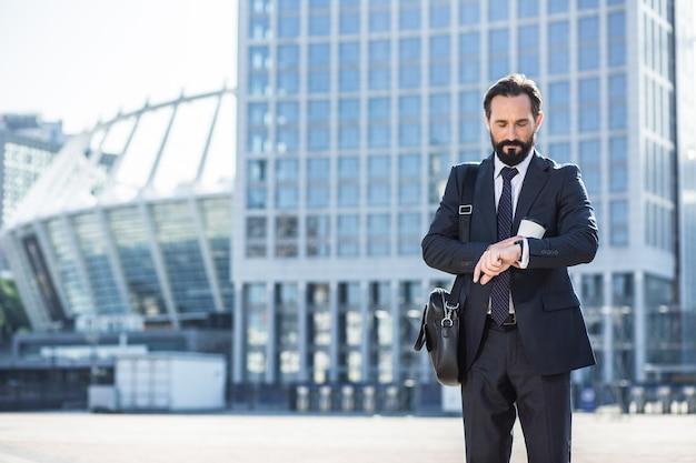 Quelle heure est-il. homme d'affaires handsoem professionnel va travailler tout en vérifiant l'heure