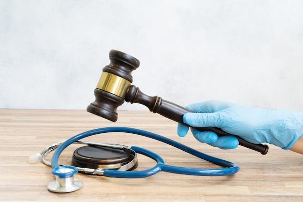 Quelqu'un a la main avec le marteau de la loi à la main, concept de droit médical