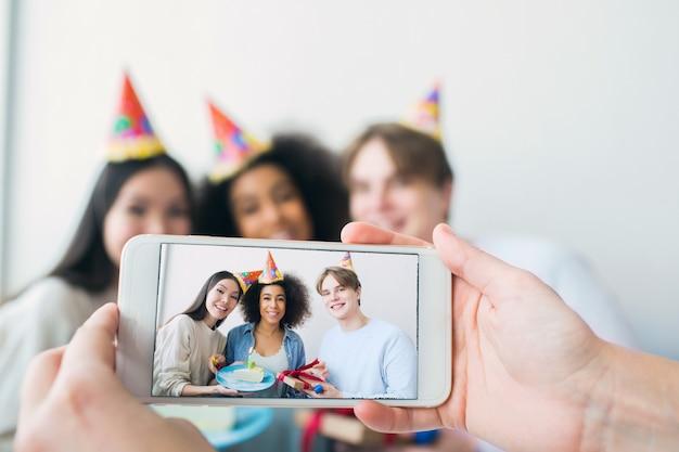 Quelqu'un prend une photo au téléphone. il y a une fille qui fête son anniversaire et ses amis qui sont réunis. ils posent et sourient à la caméra.