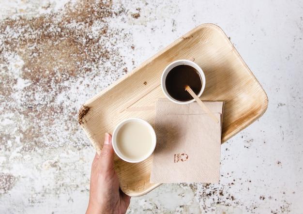 Quelqu'un tenant un plateau sans plastique avec des serviettes sans plastique et des gaz sans plastique avec du lait et du café