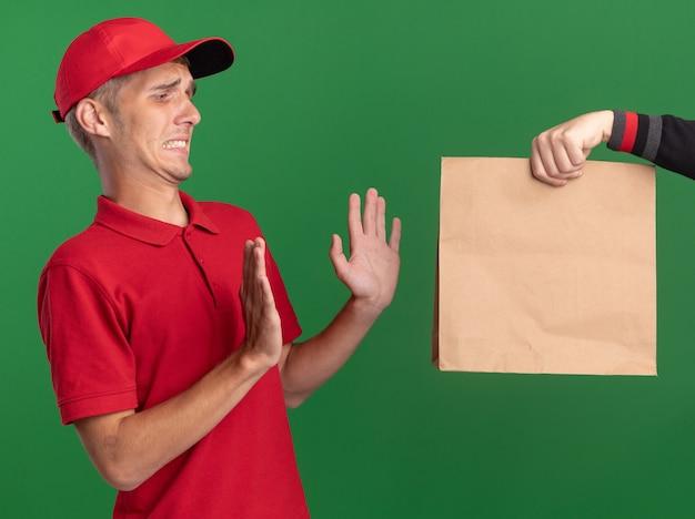 Quelqu'un tend un paquet de papier à un jeune livreur blond mécontent debout avec les mains levées isolées sur un mur vert avec espace pour copie