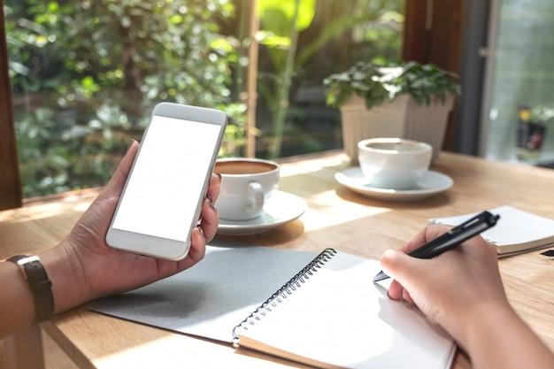 Quelqu'un tient blanc un smartphone tout en écrivant sur un ordinateur portable