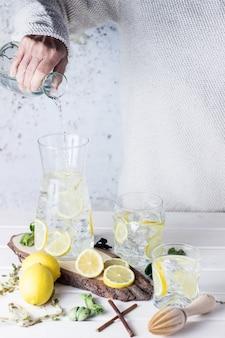 Quelqu'un versant de l'eau dans un pot tout en préparant une limonade