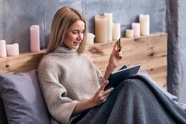 Quelque chose de nouveau. ravi jeune jolie femme shopping en ligne assis dans son lit et à l'aide de tablette.