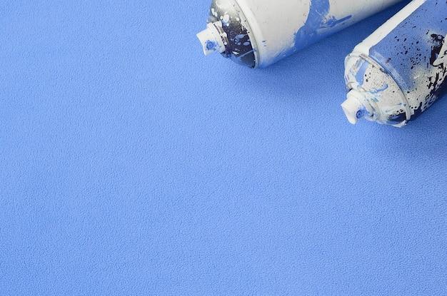 Quelques aérosols bleus usés avec gouttes de peinture