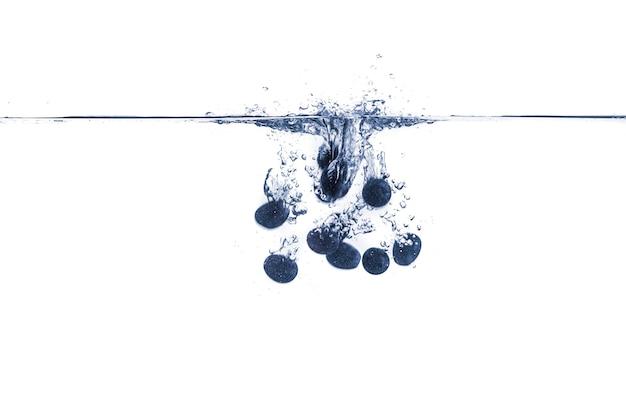 Quelques baies de raisin bleu isolées tombent dans l'eau avec des éclaboussures
