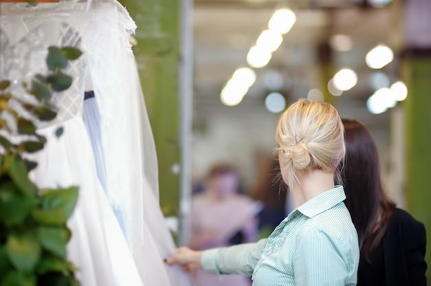 Quelques belles robes de mariée sur un cintre. deux jeune femme choisit la robe de mariée parfaite lors de courses nuptiales.