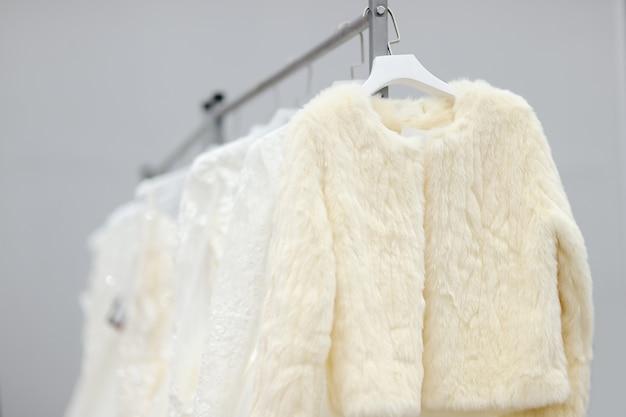 Quelques belles robes de mariée et manteau de fourrure sur un cintre. achats de mariée