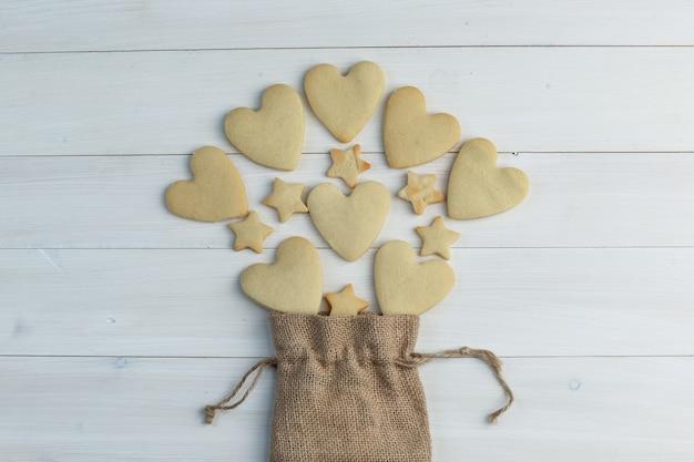 Quelques biscuits éparpillés à partir d'un sac sur fond de bois, pose à plat.