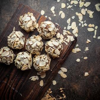 Quelques biscuits à la pistache sur bois et fond texturé noir, vue de dessus.