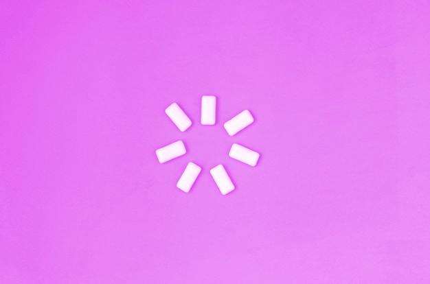 Quelques chewing-gums se trouvent sur du papier de couleur violet pastel
