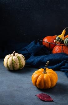 Quelques citrouilles décoratives et feuilles d'automne sur table sombre avec serviette