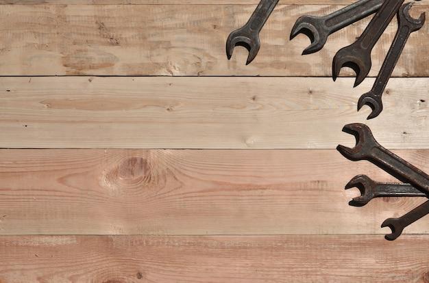 Quelques clés rouillées gisent sur une table en bois dans un atelier