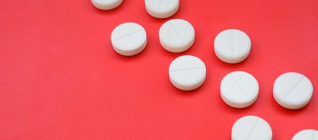 Quelques comprimés blancs se trouvent sur une surface de fond rouge vif