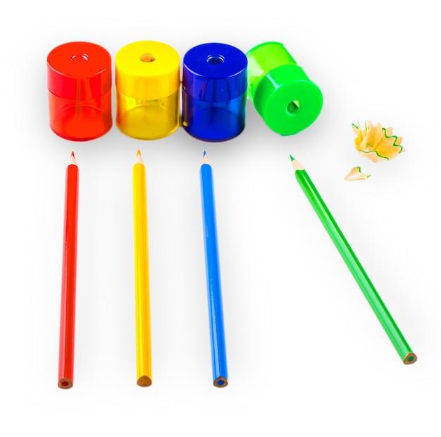 Quelques crayons de couleur de différentes couleurs et un taille-crayon et des copeaux de crayon isolés