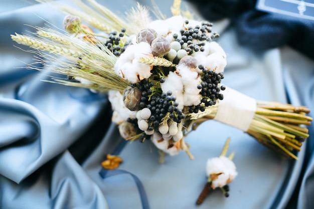 Quelques décorations de mariage, fleurs sur fond de tissu bleu, vue grand angle.