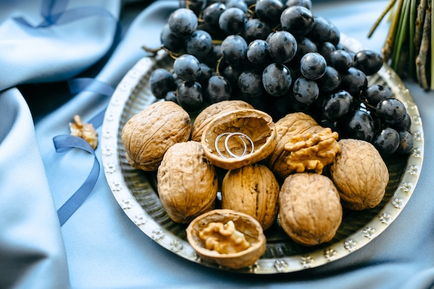 Quelques décorations de mariage avec des raisins et des noix dans une assiette sur fond de tissu bleu, vue grand angle.