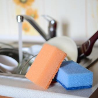 Quelques éponges reposent sur le fond de l'évier avec de la vaisselle sale