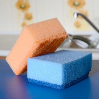 Quelques éponges se trouvent sur le fond de l'évier avec de la vaisselle sale