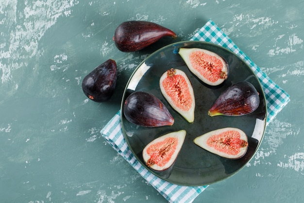 Quelques figues et moitiés de mission dans un bol et à proximité sur un tissu de pique-nique et un plat turquoise.