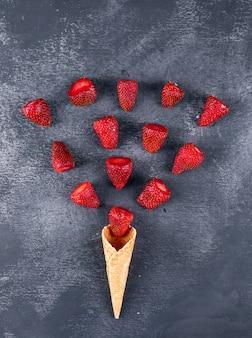 Quelques fraises formant une forme de crème glacée sur une table sombre, vue du dessus.