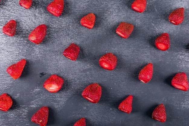 Quelques fraises sur table sombre, composition du motif