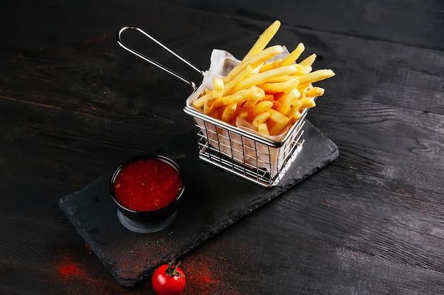 Quelques frites prêtes à être mangées et de la sauce dans un récipient