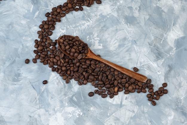 Quelques grains de café dans une cuillère en bois sur fond de plâtre gris, à plat.