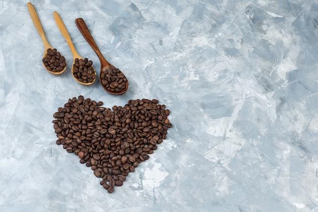 Quelques grains de café dans des cuillères en bois sur fond de plâtre gris, à plat.