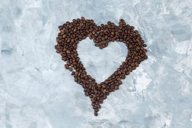 Quelques grains de café sur fond de plâtre gris, pose à plat.