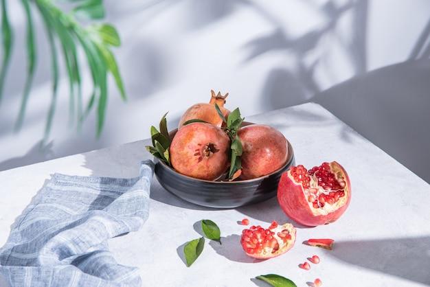 Quelques grenades rouges juteuses mûres dans une assiette sur une table lumineuse au soleil du matin. copier l'espace