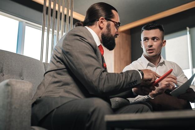 Quelques instructions. patron barbu portant un costume d'affaires donnant des instructions à son employé