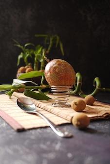 Quelques litchis, fruit de la passion et bambou sur fond sombre. style asiatique