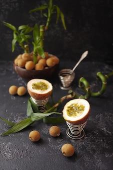 Quelques litchis, fruits de la passion et bambous sur fond sombre. style asiatique